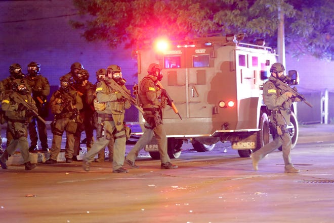 Officers in swat gear work at the intersection of West Fond du Lac Avenue and West Burleigh Street near a Jet Beauty store that was looted in Milwaukee May 30. Behind them is an armored vehicle.