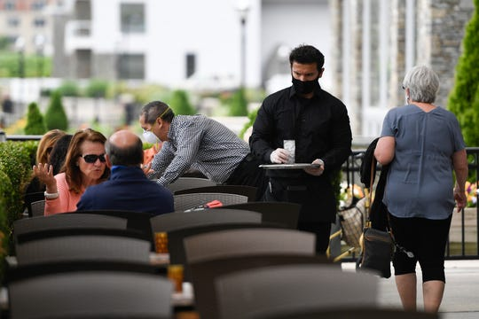Diners sit outside at Haven Riverfront Restaurant and Bar on the first day that the state is allowing restaurants to open for outdoor dining on Monday, June 15, 2020, in Edgewater. A waiter wears a face mask while serving customers.
