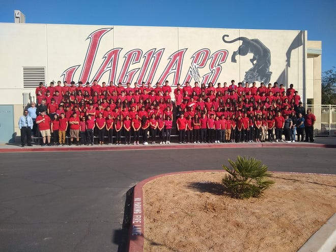 Students in a program pose for a photo outside of the Jaguars' building.