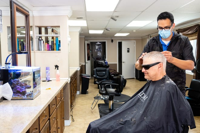 Charles Darghali, right,  gives Dave Fuller, of Port Huron, a haircut Monday, June 15, 2020, at Salon Shear Brilliance in Fort Gratiot. Darghali, who's owned the salon for around 12 years, was able to open his salon for the first time in months Monday after restrictions from Gov. Gretchen Whitmer's stay home order begin to ease.