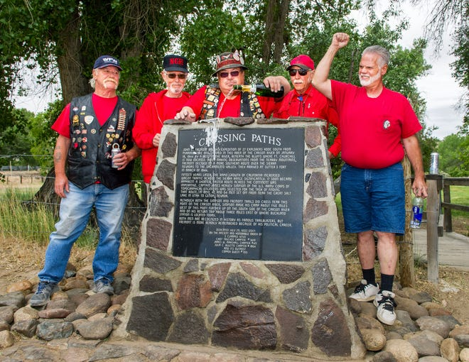 """Stacy Wilhelmi, center, christens a plaque commemorating the """"Crossing Paths"""" of John C. Fremont and U.S. Army Corp of Engineers Captain James Hervey Simpson. Left to right, Rich Wilson, representing Copper Queen 1915, George Mortimer, Chief Truckee 3691, Wilhelmi, Copper Queen 1915, Gene Duncker, Julia C. Bluette 1864, Craig Poupeney, Chapter 49."""