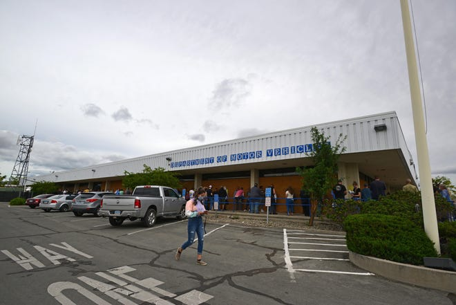 People stand in line to enter the Department of Motor Vehicles in Reno, Nev. The DMV temporarily suspended driving tests across the state because of concerns over spreading the novel coronavirus.