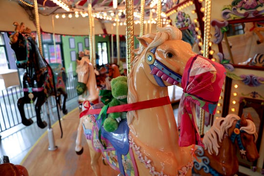 Gigi the horse wears a mask while carrying a stuffed animal on her back at the Riverfront Carousel in Salem, Oregon, on Friday, June 12, 2020. The middle row of animals is sectioned off to allow space for social distancing.