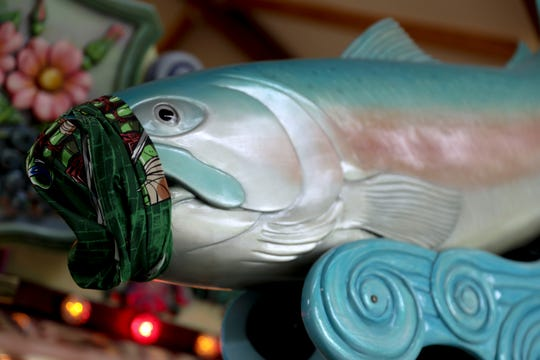 A face covering is seen on a hand-carved fish at the Riverfront Carousel in Salem, Oregon, on Friday, June 12, 2020.