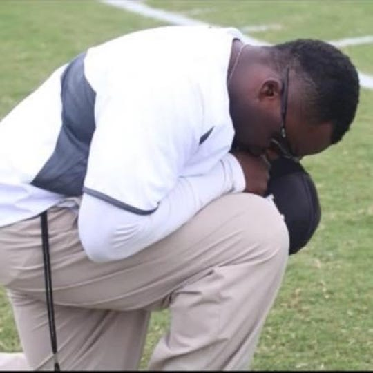 Former Angelo State football player Tyrell McCrea, now a coach at San Antonio Madison High School, takes a knee before a game.