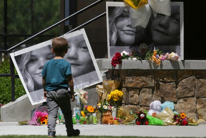 "A boy checks out a memorial for Tylee Ryan, 17, and Joshua ""JJ"" Vallow, 7, at Porter Park in Rexburg, Idaho on Thursday, June 11, 2020. (John Roark/The Idaho Post-Register via AP)"