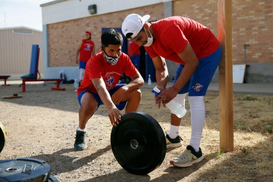 Irvin High School football players Isaac Guerrero and Joe Gomez sanitize workout equipment during offseason workouts Monday, June 15, at Irvin High School in El Paso. The team and coaches did temperature checks before practice, had hand sanitizer available and practiced social distancing during workouts.