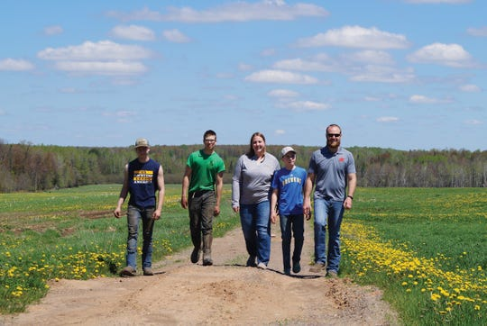 The Klussendorf family - Ryan and Cheri, Kale, Max, and Owen - walk down the lane between pastures. Normally, their dairy cows would be grazing behind them but for right now they are being temporarily housed in a neighbor's barn.