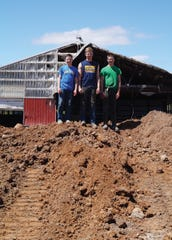 The Klussendorfs' sons stood on top of a pile of dirt where their old dairy barn stood. A section of the barn was salvaged and can be seen in the background with some damage. Construction is underway for the new barn. The family is hopeful the process of rebuilding will go quickly.