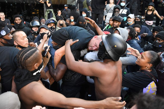A man is lifted up and taken to police lines after being beaten in clashes between protesters supporting the Black Lives Matter movement and opponents in central London on June 13, 2020.