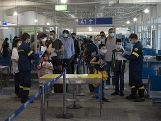 ATHENS, GREECE - JUNE 15: A firefighter directs passengers who arrived from Rome to Eleftherios Venizelos International Airport on June 15, 2020 in Athens, Greece. The country removed most restrictions on travel from EU countries today in an effort to jumpstart its tourist season. Travelers from countries deemed high-risk, like the UK countries, will still face compulsory Covid-19 testing and mandatory quarantine. One week for a negative result; two weeks for a positive result.