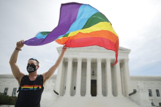 Joseph Fons holding a Pride Flag, stands in front of the U.S. Supreme Court building after the court ruled that LGBTQ people can not be disciplined or fired based on their sexual orientation June 15, 2020 in Washington, DC. With Chief Justice John Roberts and Justice Neil Gorsuch joining the Democratic appointees, the court ruled 6-3 that the Civil Rights Act of 1964 bans bias based on sexual orientation or gender identity.