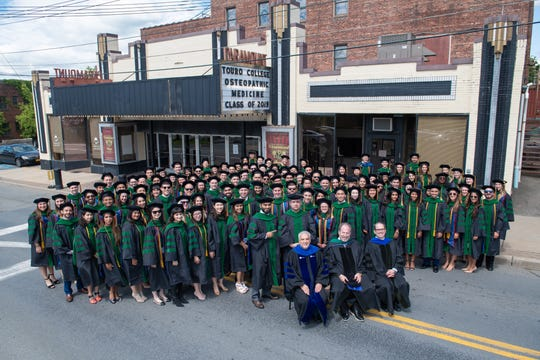 Touro College of Osteopathic Medicine Executive Dean Kenneth Steier, Jerry Cammarata, COO and dean of student affairs, and Stephen Jones, Touro's preclinical dean, pose with graduates outside the Paramount Theatre in Middletown, during the medical school's July 2019 commencement