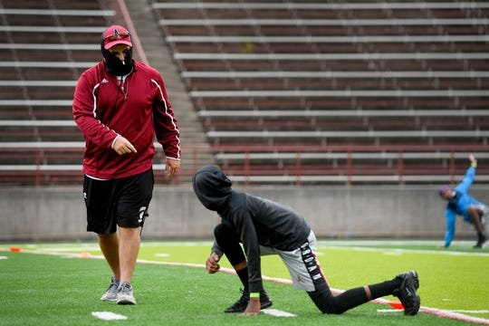 """Asheville High football coach Cort Radford talks to freshman Nicolas Williams during warmups at practice June 16, 2020. Williams said he was """"very excited"""" for the sport to return and that he was still getting used to the high school level."""