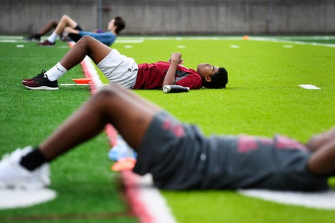 """Jeremiah Jones takes a breath after doing crunches with his team during practice at Asheville High School June 16, 2020. """"I'm excited and ready to start sports again,"""" said the freshman."""
