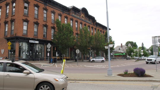 In this June 9, 2020, photo, a car passes through downtown Winooski, Vt. Members of the town's immigrant community said they have been hit hard by the virus that causes COVID-19. The Vermont Health Department is working to contain the outbreak.