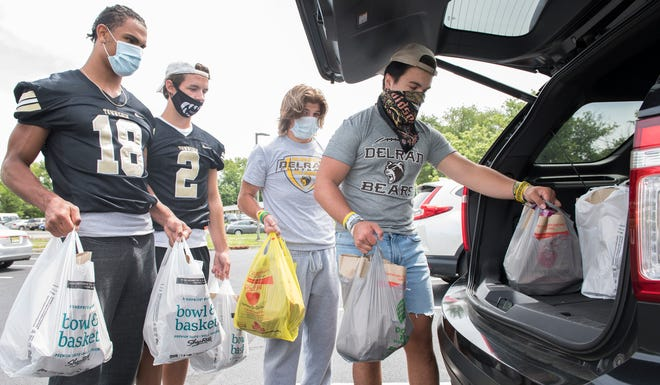 (From right to left); Delran's Jason Holmes, Delran's Jake Baumann, Burlington Township's Gage Miller, and Burlington Township's Jordan Dotson load a vehicle with donated food as the football players take part in a food drive at Sports Paradise in Delran on Monday, June 15, 2020.