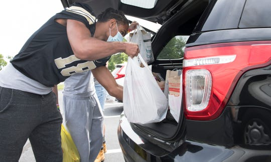 Burlington Township High School football player Jordan Dotson loads a vehicle with donated food as Dotson takes part in a food drive at Sports Paradise in Delran on Monday, June 15, 2020.