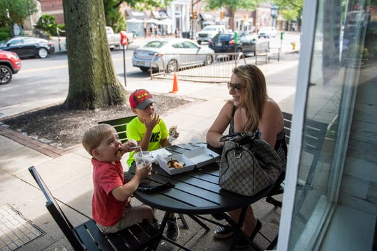 Amanda Greenstein, from right, John Shultz, 7, and Oliver Shultz, 3, enjoy donuts from Haddonfield Donut and Bakery in downtown Haddonfield, N.J. as restaurants and business continue to reopen Tuesday, June 16, 2020.