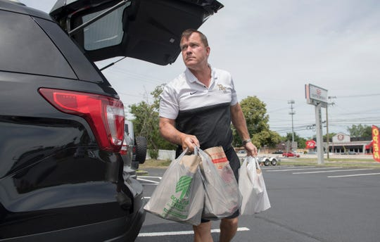 Burlington Township High School football coach Tom Madeira unloads donated food from a vehicle as Madeira takes part in a food drive at Sports Paradise in Delran on Monday, June 15, 2020.