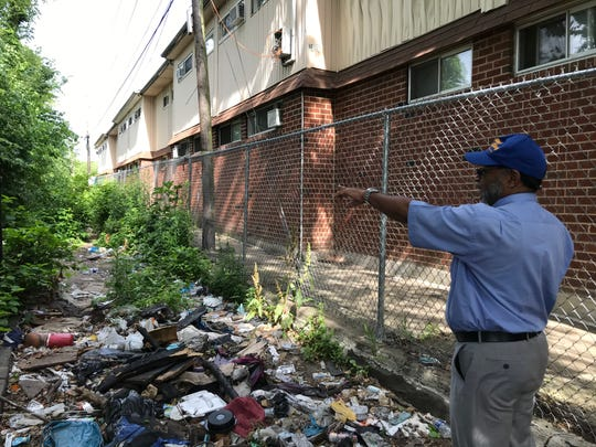 Father Gerard Marable, who presides over services at St. Bartholomew Church, points to trash and debris left behind by drug users and dealers in an alley next to the church and its rectory.