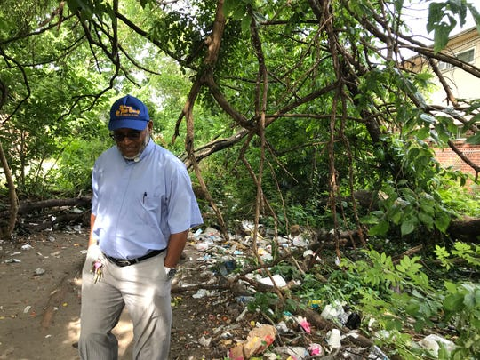 Father Gerard Marable walks through a clearing in an overgrown area off Kaighn Avenue in Camden where drug users congregate.