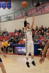 Cruz McFadden wears a brace on his arm as he takes a jump shot. The pain in his elbow affected McFadden's three-point shot and lead to his Tommy John surgery.