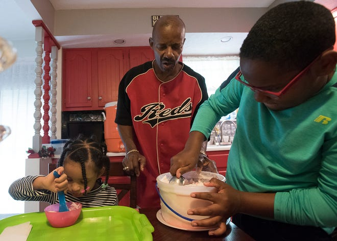Johnny Jones holds the ice cream container as his son Jordan scoops some out Sunday afternoon in Chillicothe. The Jones were forced to stay inside due to rain.