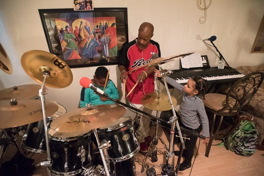Aniyah Jones tries to get the attention of her father as he gives her brother Jordan drum lessons in the basement of their Chillicothe home on June 14, 2020.