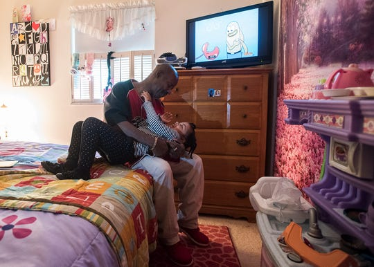 Johnny Jones tickles his daughter Aniyah after she finished playing a V-Tech game in her room in Chillicothe, Ohio.