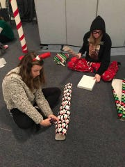 Haley Resta (foreground) packing care packages for families in need shortly before Christmas.