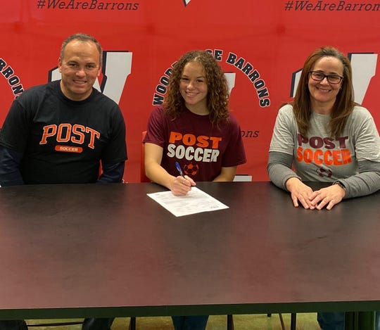 Leticia Da Silva (center) with her parents as she signs a letter of intent to play soccer at Post University