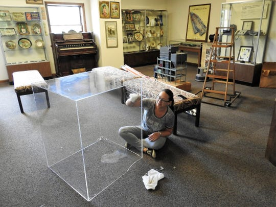 Kristin Cheney polishes a display case in the upstairs foyer of the Johnson-Humrickhouse Museum. The museum is reopening on Friday following renovations and COVID-19 pandemic closures.