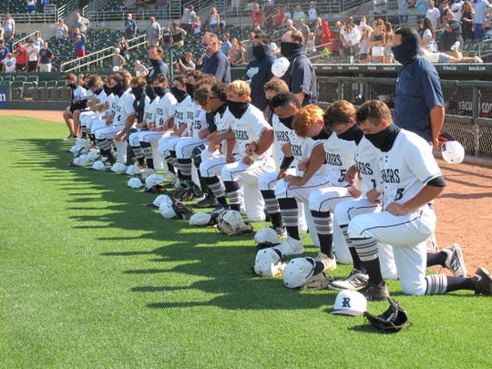 Members of the Des Moines Roosevelt baseball team kneel during the national anthem ahead of their game against Ankeny Centennial at Principal Park in Des Moines on Monday, June 15, 2020.