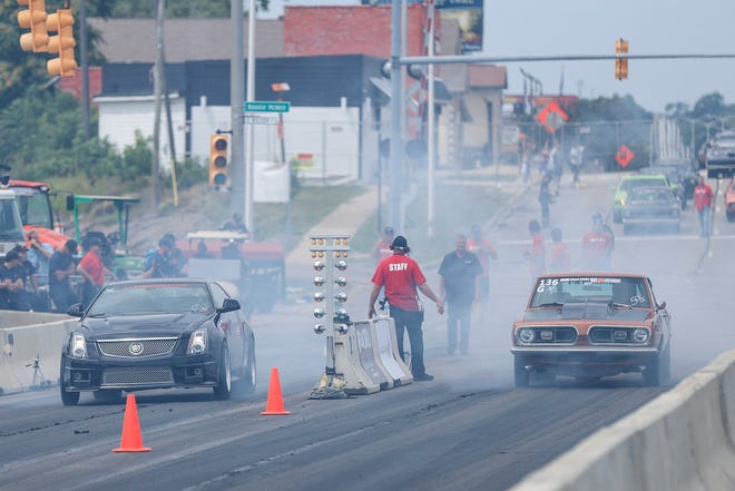 Amateur drag racers compete on a closed section of Woodward Avenue near the M1 Concourse in Pontiac during Roadkill Nights Powered by Dodge on August 11, 2018.