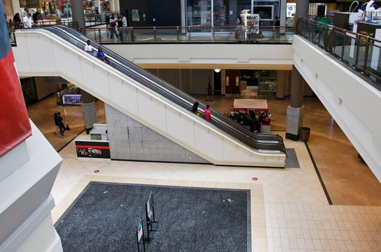 In this May 1, 2020, file photo, people ride down an escalator at a shopping mall in Oklahoma City as it reopens from its closure since mid-March due to coronavirus concerns.