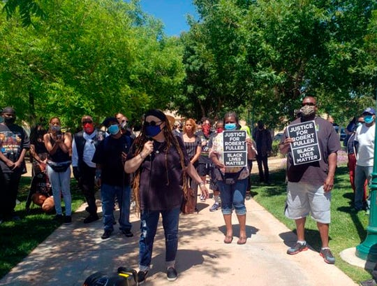 """In this Saturday, June 13, 2020, photo provided by Najee Ali, people gather around the park where the body of Robert Fuller was found dead. People marched to demand an investigation. The protesters marched from where the body was found to a sheriff's station, with many carrying signs that said """"Justice for Robert Fuller."""""""