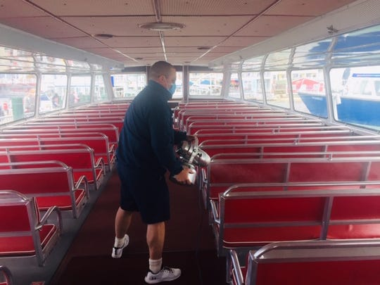 A Shepler's Mackinac Island Ferry worker spray sanitizes the lower level of a boat after its arrival at Mackinac Island.