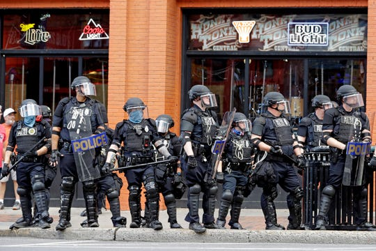 In this June 4, 2020, file photo, Metro Police officers watch as marchers in a protest pass through downtown Nashville, Tenn.