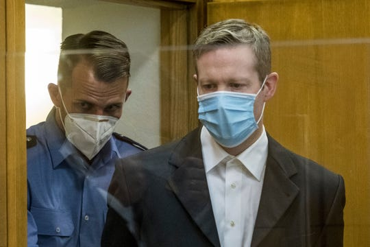 Defendant Stephan Ernst, right, who is accused of murdering politician Walter Luebcke he arrives for the first day of his trial at the Oberlandgericht Frankfurt courthouse, in Frankfurt, Germany, Tuesday, June 16, 2020.