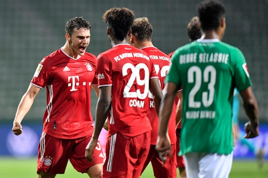 Bayern's Benjamin Pavard, left, celebrates with his teammates Bayern's Kingsley Coman and Bayern's Joshua Kimmich end of the German Bundesliga soccer match between Werder Bremen and Bayern Munich Tuesday in Bremen, Germany, Tuesday, June 16, 2020. Because of the coronavirus outbreak all soccer matches of the German Bundesliga take place without spectators.