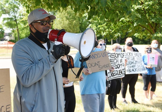 Rev.W.J. Rideout, (with bullhorn) of Defender of Truth & Justice leads the rally at the Shelby Township Police Dept.
