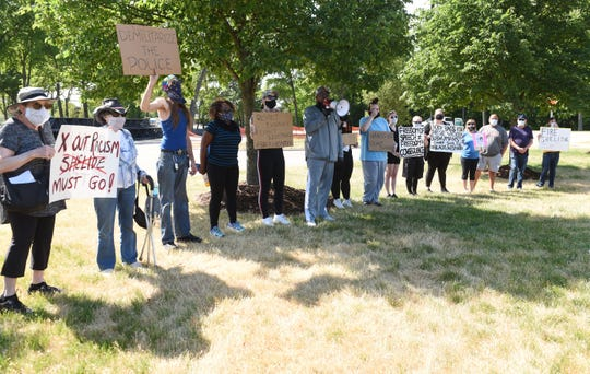 Rev.W.J. Rideout, (c, with bullhorn) of Defender of Truth & Justice leads the rally at the Shelby Township Police Dept.