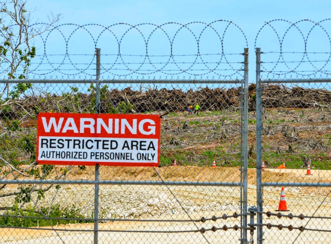 Contract workers can be seen in the distance beyond a perimeter fence enclosing the ongoing construction of the Marine base in Dededo in this June 16 file photo.