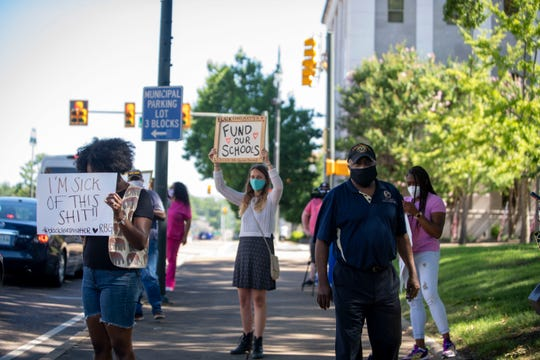 """Camille Sikes holds up a sign reading """"Fund our Schools"""" with NAACP President Harrell Carter and other protestors in front of the Madison County Courthouse, Tuesday, June 16, 2020."""