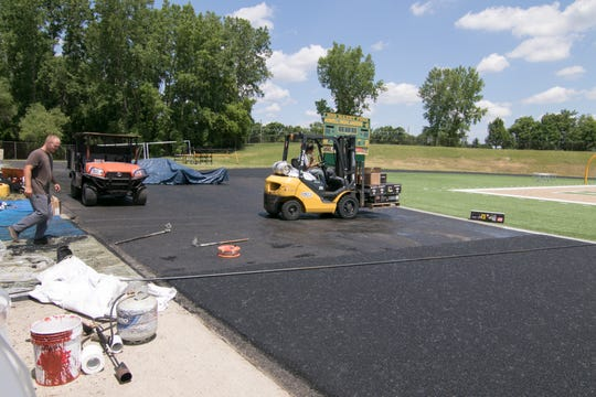 Star Trac Enterprise workers finish the first layer of rubber on Howell High School's track Tuesday, June 16, 2020.