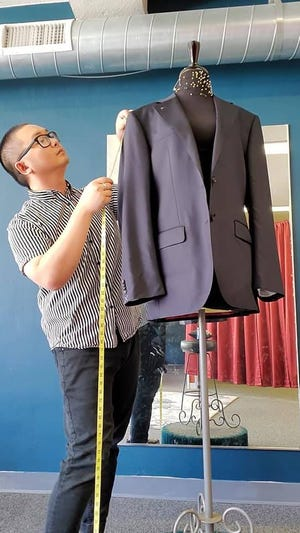 Tou Fong, co-owner of OutKast Alterations in Menomonee Falls, makes alterations to a blazer. Outkast Alterations is the state's first Hmong LGBTQIA+ business.
