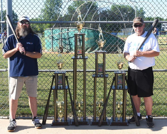 Lockeroom owner Jason Wingate (left) and Lockeroom head coach Lester White show off the trophies and bats that will be awarded Sunday at the conclusion of the 34th annual Mickey Huskey Twin Lakes Classic at Cooper Park.