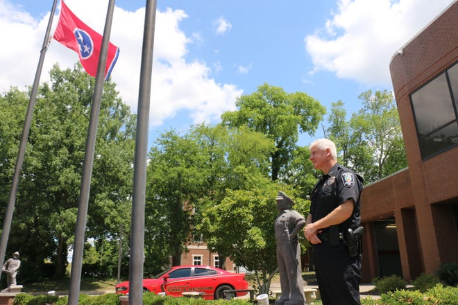 Tommy Walsh stands next to a statue of a police officer outside Brentwood City Hall on June 15.