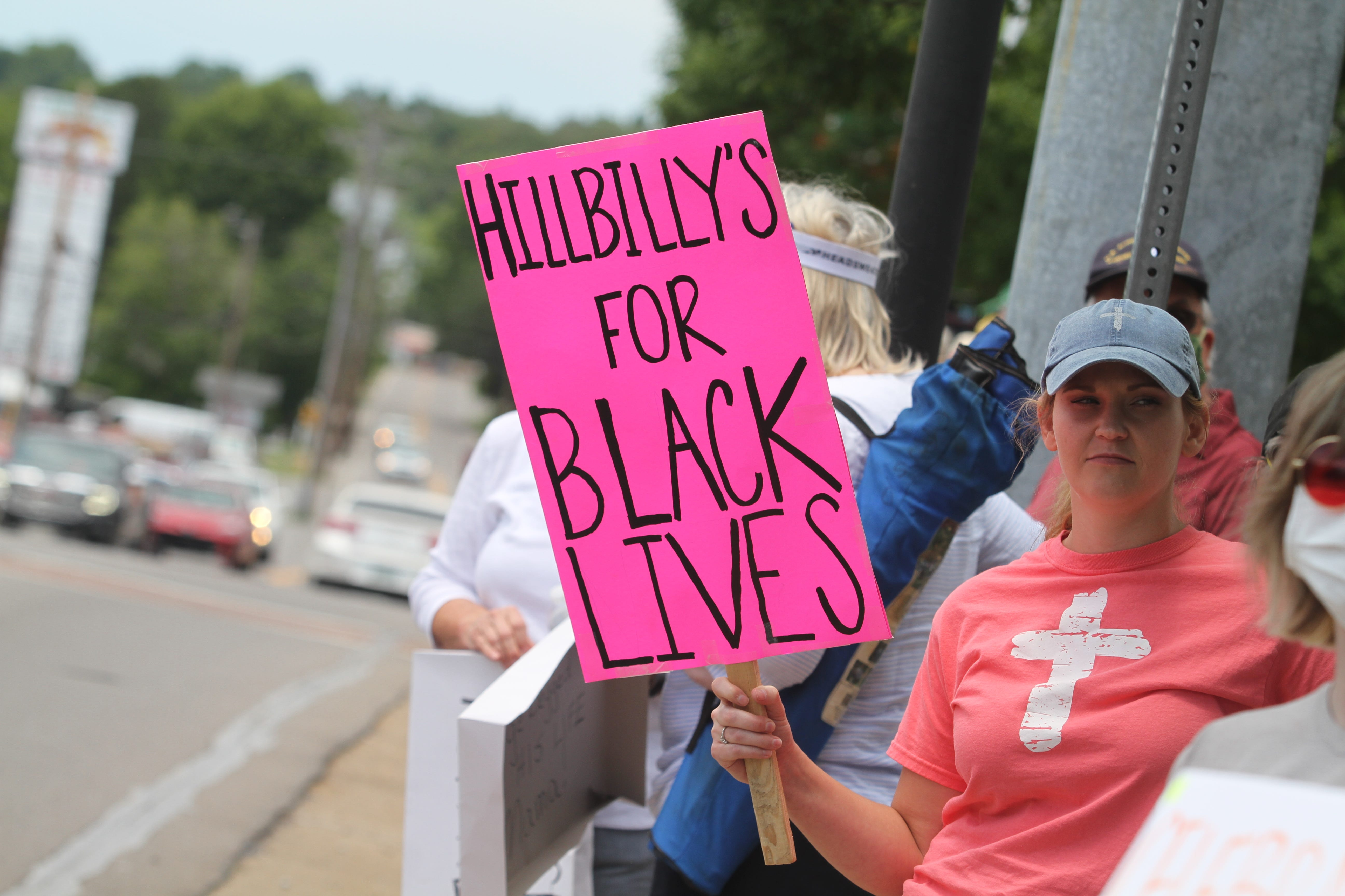 """A woman holds a sign during an anti-racism rally in Ashland City, Tenn., on June 14. Across the street, another group countered with """"All Lives Matter,"""" while waving American and Confederate flags."""